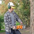 Man cutting log into sections with chainsaw — Stock Photo