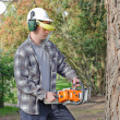 Royalty-Free Stock Photo: Man cutting log into sections with chainsaw