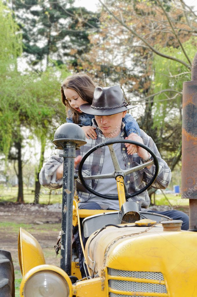 Father and daughter sitting on the old farm tractor — Stock Photo #7362508