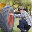 Handsome next to a tractor wheel fixing — Stock Photo