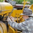 Portrait of a farmer on the tractor fixing — Stock Photo