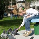 Little girl feeding Pigeons in the park — Stock Photo #7949956