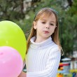 A beautiful little girl playing with balloons in the park — Stock Photo