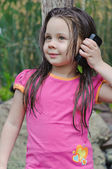 Little girl talking to a cell phone — Stock Photo