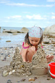 Girl building sandcastles on the beach — Stock Photo