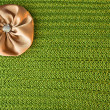 Background with a green knit texture and brown bow - Stock Photo