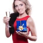 Девушка в красном платье с бокалом и подарком — Stock Photo