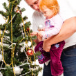 Foto Stock: Dad with daughter decorate new-year tree