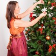 Stock Photo: Young womdecorating fir-tree