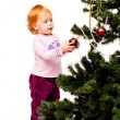 A little girl decorates a new-year tree — Stock Photo