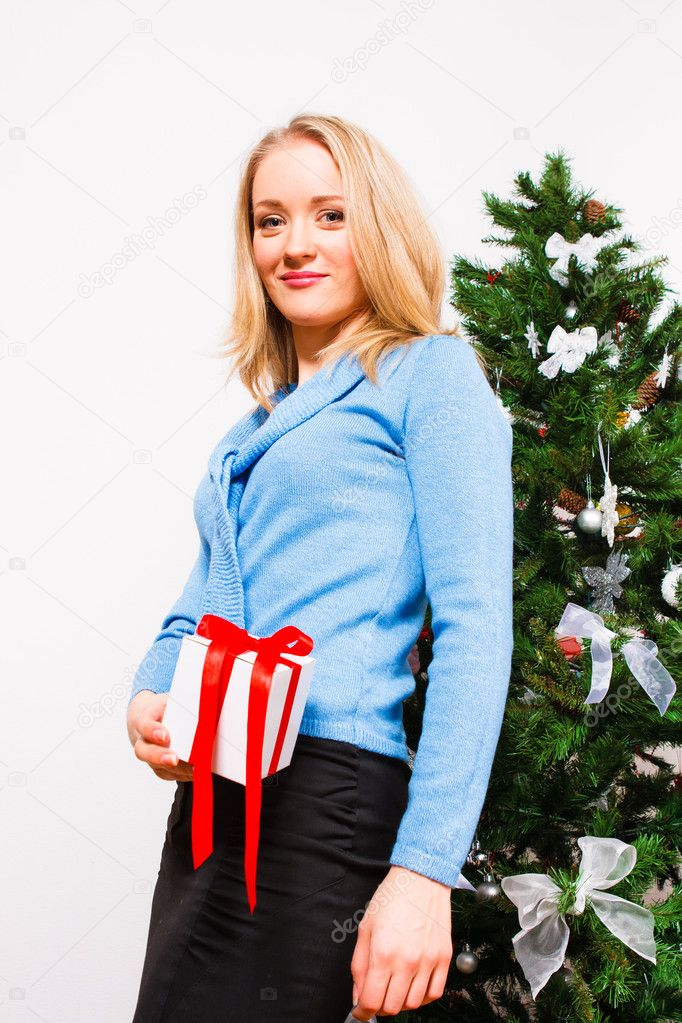 Young  woman  with a gift near  a new-year tree — Stock Photo #7074190