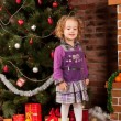 Little girl staying near Christmas tree - Stockfoto