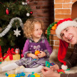 Little girl play with dad near Christmas tree — 图库照片