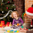 Little girl play with dad near Christmas tree — Stock Photo #7412733