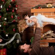 Little girl play with dad  near Christmas tree - Zdjęcie stockowe