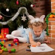 Little girl drawing near Christmas tree - Stockfoto