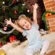 Little girl sitting near Christmas tree - Stockfoto