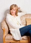 Young woman sits on a sofa — Stock Photo