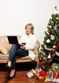 Young woman with a notebook near Christmas tree — Stock Photo