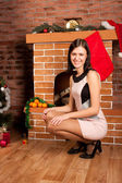 Beautiful woman near fire-place at christmas time — Stock Photo