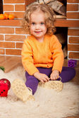 Little girl sitting near fireplace — Stock Photo