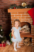 Little girl staing near fireplace — 图库照片