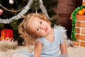 Little girl sitting near Christmas tree — Stock Photo