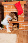 Little girl looking up fireplace — 图库照片