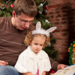 Little girl with her dad near Christmas tree — Stock Photo #7792837