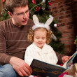 Little girl with her dad near Christmas tree — Stock Photo #7792843