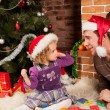Little girl play with dad  near Christmas tree — Stok fotoğraf
