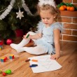 Little girl drawing near Christmas tree — Stock Photo