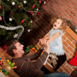 Little girl play with dad  near Christmas tree — Zdjęcie stockowe