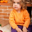 Little girl sitting near fireplace - Stockfoto