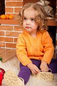 Little girl sitting near fireplace — Stock Photo