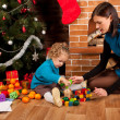 Stock Photo: Mother and her daughter near Christmas tree