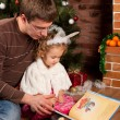 Little girl with her dad near Christmas tree - Stock Photo