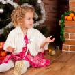 Stock Photo: Little girl sitting near Christmas tree