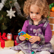 Little girl play near Christmas tree - Stockfoto