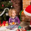 Little girl play with dad  near Christmas tree - Stockfoto