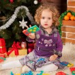Stock Photo: Little girl play near Christmas tree