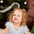 Little girl sitting near Christmas tree — Stock Photo #7961239
