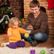Stock Photo: Little girl play with dad near Christmas tree
