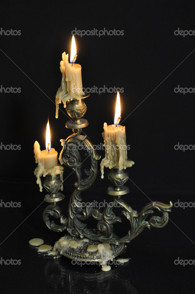 Antique candelabra with three melting candles on black background — Stockfoto #7359732
