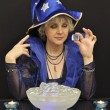Witch in blue hat with magic crystals and candles - Stock Photo
