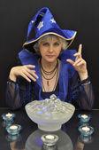 魔法の結晶やキャンドルで青い帽子の魔女します。 — ストック写真