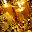 Gold christmas candles and gold gift boxes - Stock Photo