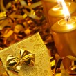 Foto Stock: Gold christmas candles and gold gift boxes