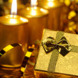 Gold christmas candles and gold gift boxes — Stock Photo