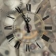 Old hours with figured arrows on mechanism blur background — Foto Stock